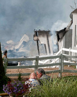 Farm owner looks on as firefighters fight fire